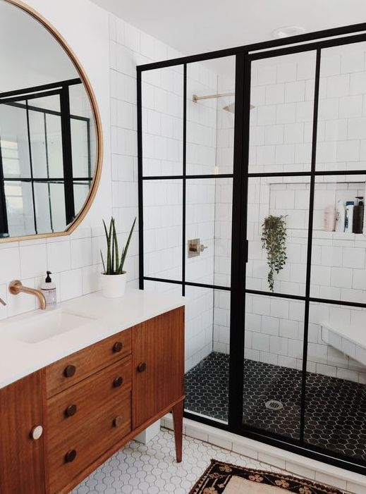 a lovely mid-century modern bathroom with white subway, black adn white penny tiles, a stained vanity, a round mirror and a shower