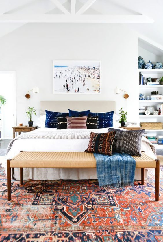 a lovely mid-century modern bedroom with a neutral upholstered bed, printed bedding and a rug, a woven bench, stained nightstands and a photo
