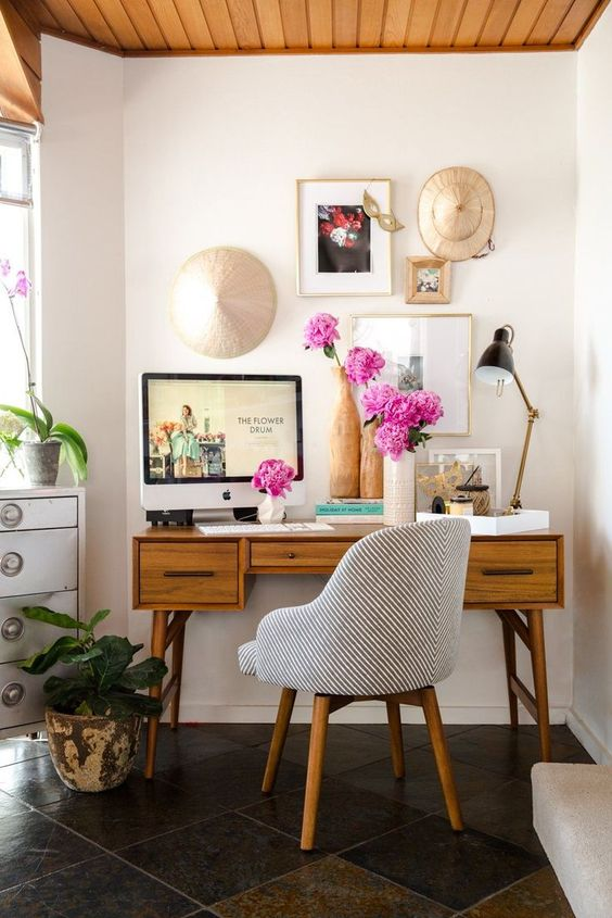 a lovely mid-century modern home office nook with a delicate desk, a striped chair, a pretty gallery wall, potted plants and blooms