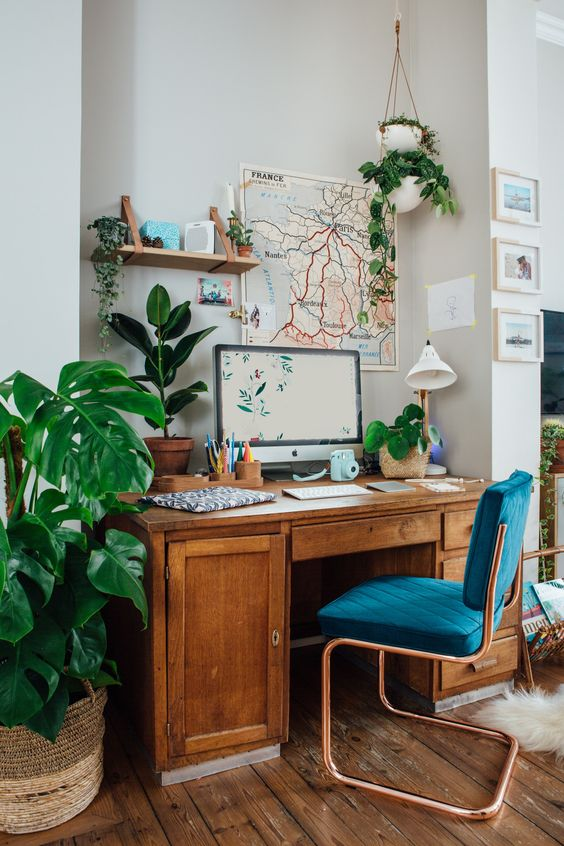 a lovely mid-century modern home office nook with a stained desk, a navy chair, potted plants, a map artwork and a mini gallery wall