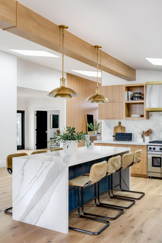 a lovely mid-century modern kitchen with light-stained cabinets, a white chevron backsplash, a navy kitchen island with a white marble countertop