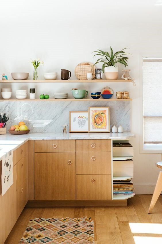 a lovely mid-century modern kitchen with light-stained cabinets, a white stone countertop and a backsplash, open shelves