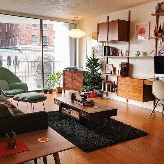 a lovely mid-century modern living room with a green chair and a footrest, a black sofa, chic rich stained wooden furniture and potted plants