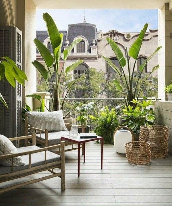 a lovely modern balcony with rattan furniture, potted greenery, a lantern and baskets is a cool space to enjoy outdoors and fresh air
