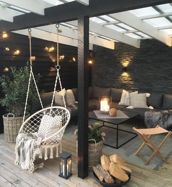 a lovely modern patio with a touch of boho, with wicker and metal furniture, a hanging macrame chair, potted greenery, candle lanterns and firewood