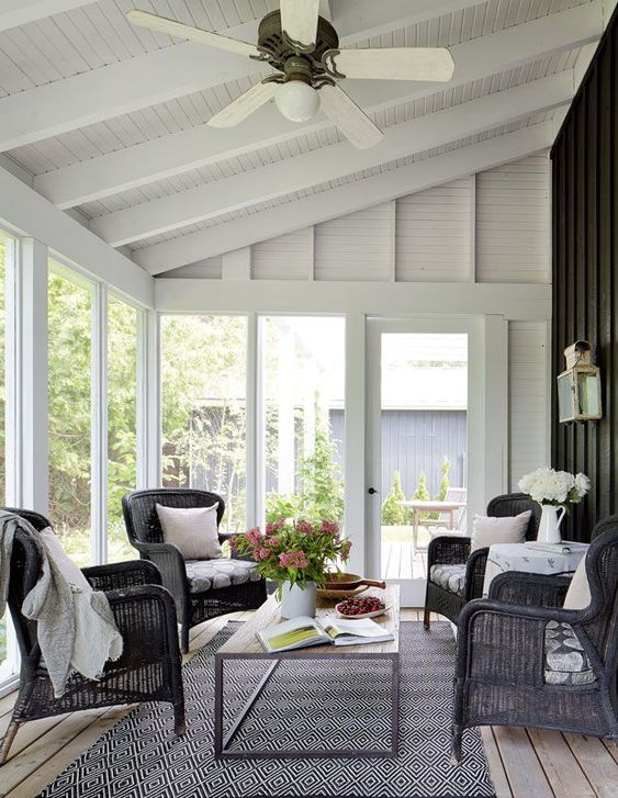 a lovely modern screened porch with black wicker chairs, a low coffee table, some potted flowers and plants is an amazing outdoor living room