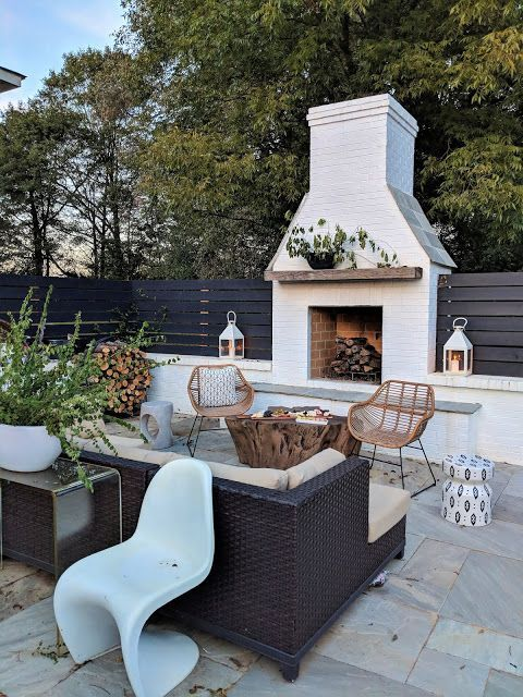 a lovely modern terrace with a white brick fireplace, rattan and wicker furniture, potted greenery, firewood and pretty side tables