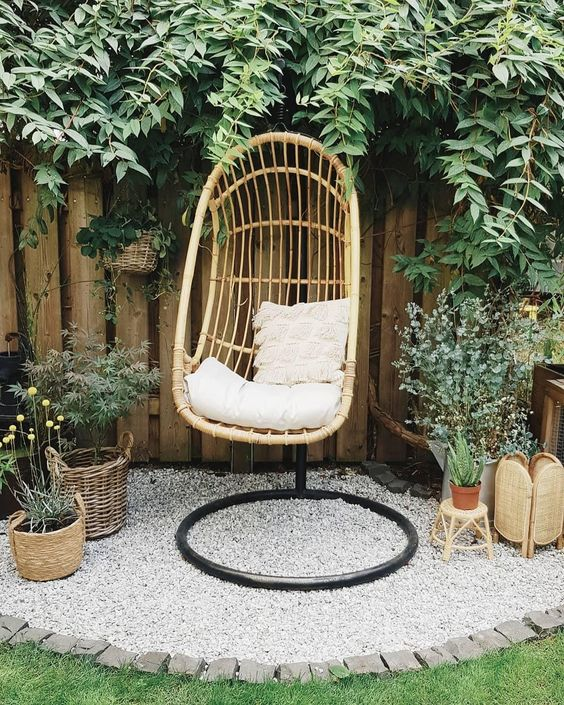 a lovely outdoor nook just for one, with a hanging chair on a stand and lots of potted greenery and blooms