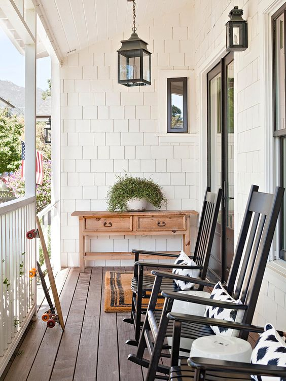 a lovely porch with a stained console, black rockers, printed textiles, hanging lanterns and potted greenery is a cool idea