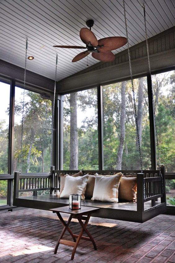 a lovely screened porch with a birck floor, a hanging black bench, a small folding table and gorgeous views of the forest around