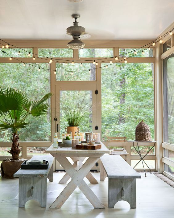 a lovely screened porch with a white trestle table, shabby chic benches, side tables, potted plants and some string lights