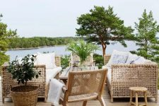 a lovely terrace with a wooden deck, woven rattan furniture, neutral and printed textiles, potted greenery and a gorgeous lake view