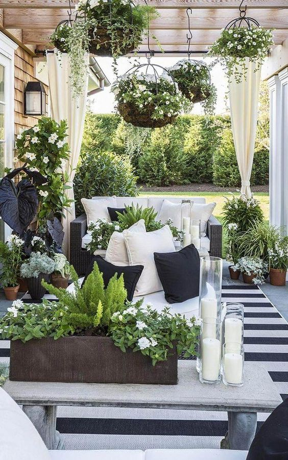 a lovely terrace with black wicker furniture, a stone coffee table, lots of potted greenery and blooms hanging and standing around
