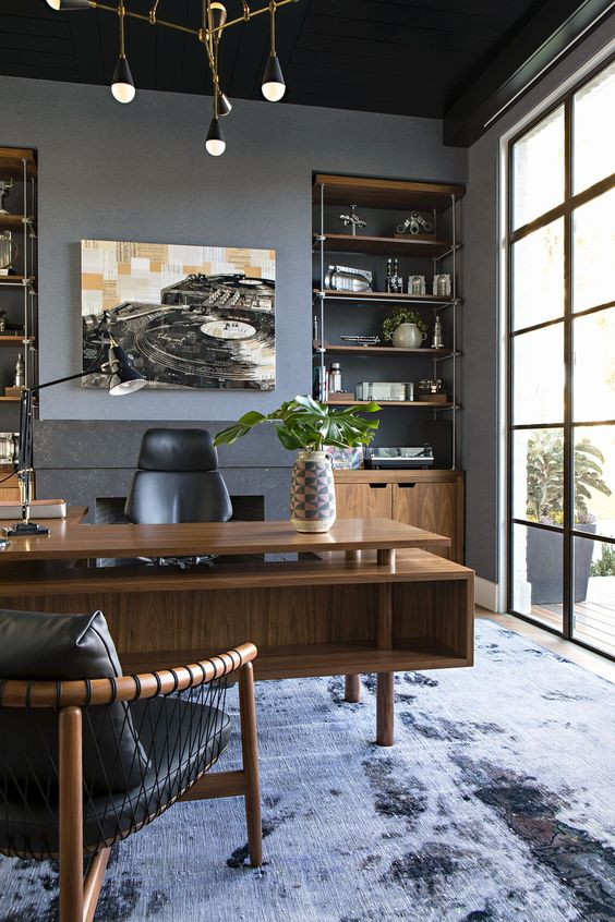 a luxurious mid-century modern home office with grey walls, a glazed wall, a stained desk, built-in storage units and shelves and leather furniture