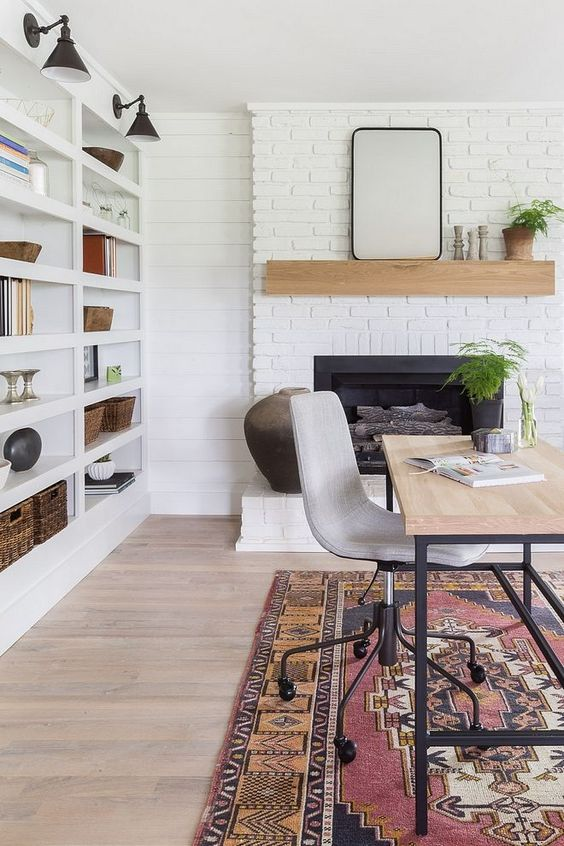 a lovely modern farmhouse home office with a white brick fireplace, a mantel, a large shelving unit with sconces, a delicate desk and printed rug