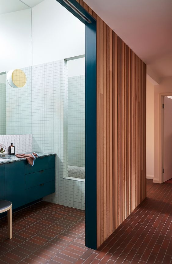 a mid-century modern bathroom with a red brick floor, a teal vanity, ligth green tiles covering the bathtub space