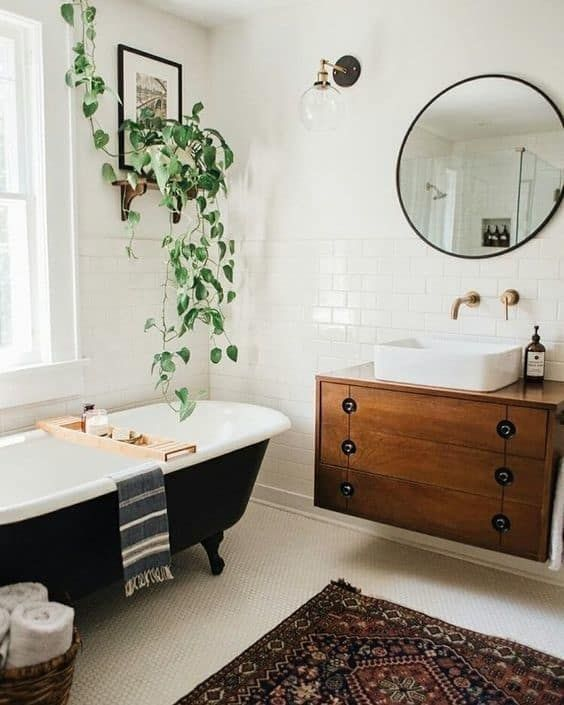 a mid-century modern bathroom with different white tiles, a black clawfoot tub, a floating vanity, potted greenery and a round mirror