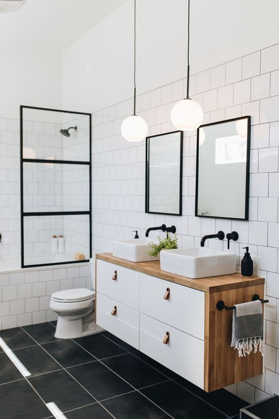 a mid-century modern bathroom with long grey tiles and white square ones, black frames and a floating vanity with two sinks