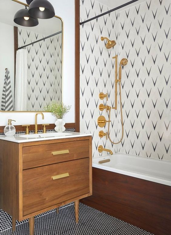 a mid-century modern bathroom with penny tiles, an accent wall in the shower, a stained vanity, gold fixtures