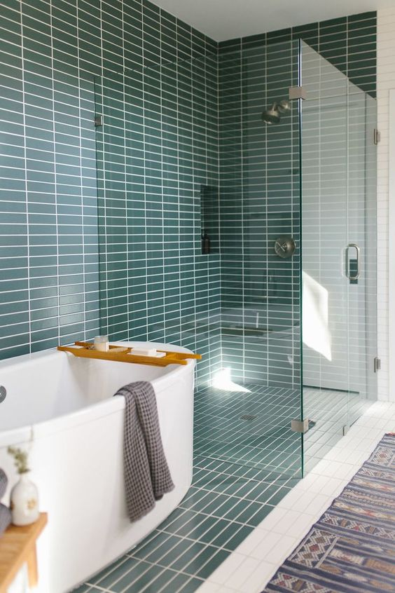 a mid-century modern bathroom with teal skinny tiles, a white tub and a printed rug is a very welcoming space