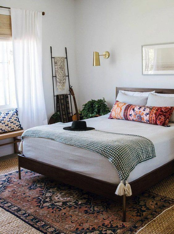 a mid-century modern bedroom with a dark stained bed, a woven bench, a ladder for hanging stuff, gold sconces and printed textiles