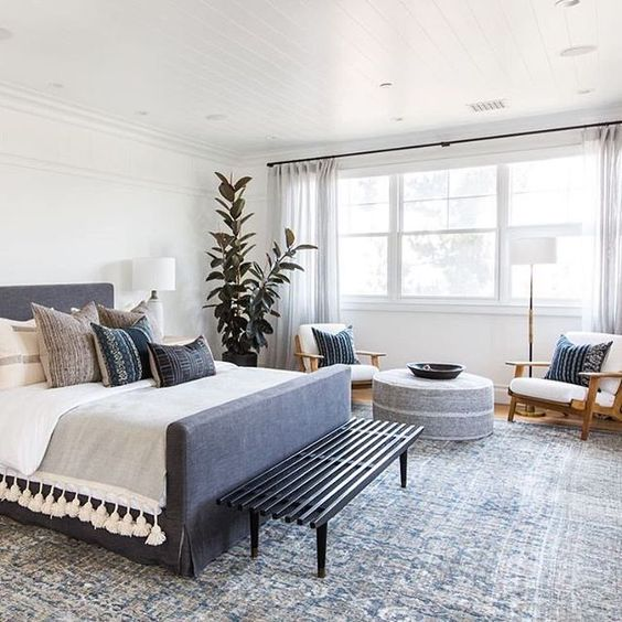 a mid-century modern bedroom with a grey upholsteed bed with printed pillows, a grey ottoman and a cool chair, a black bench and potted plants