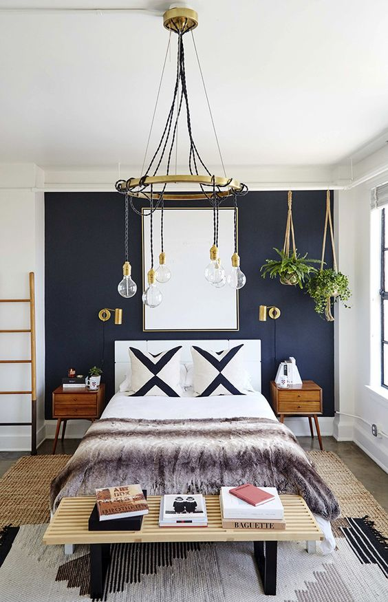 a mid-century modern bedroom with a navy accent wall, a white bed, a wooden bench, stained nightstands, a chic chandelier, potted greenery and a cool rug