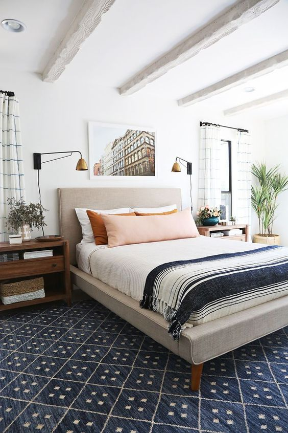 a mid-century modern bedroom with an upholstered bed, stained nightstands, brass scones, a pretty photo and printed textiles