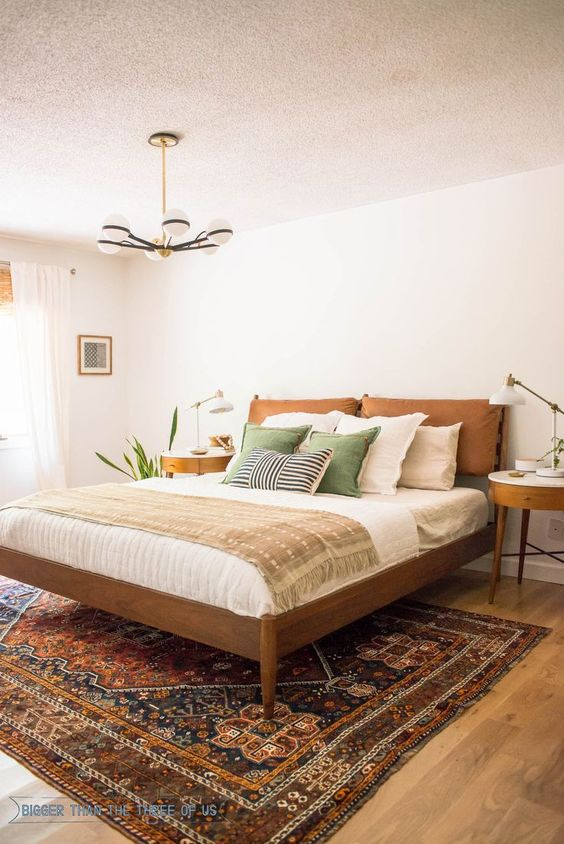 a mid-century modern bedroom with elegant stained furniture, green and printed bedding, a printed rug, potted plants and a chic chandelier