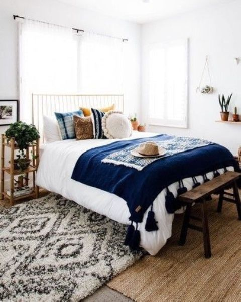 a mid-century modern boho bedroom with a metal bed, wooden nightstands, a wooden bench, printed pillows and a rug