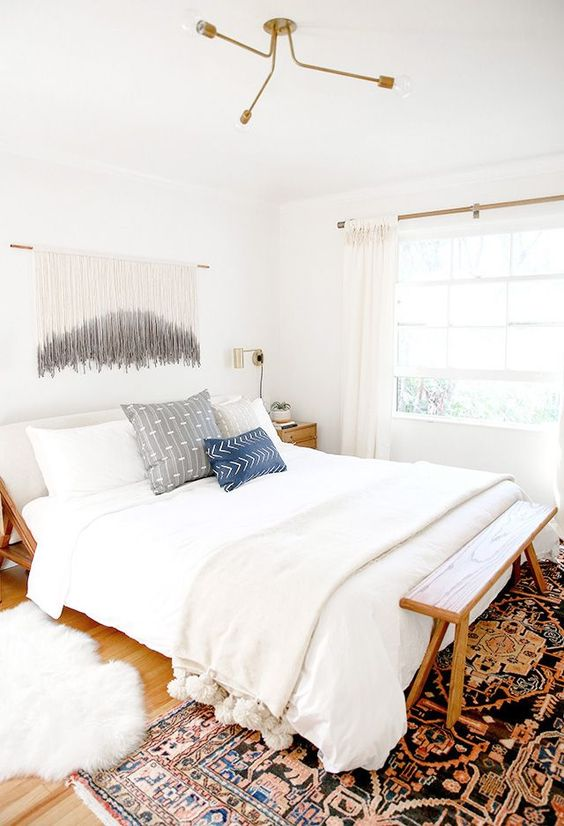 a mid-century modern boho bedroom with stained furnniture, neutral bedding and printed pillows, a macrame hanging, a bold printed rug