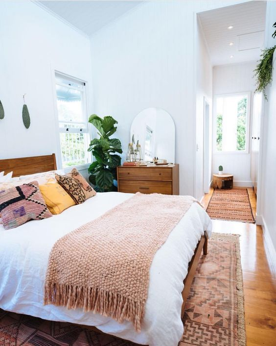 a mid-century modern farmhouse bedroom with stained furniture, neutral and printed bedding, potted greenery, a rounded mirror and a printed rug