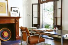a mid-century modern home office with an entrance to the blacony, a non-working fireplace, a desk, an orange leather chair, a printed rug and chic artworks