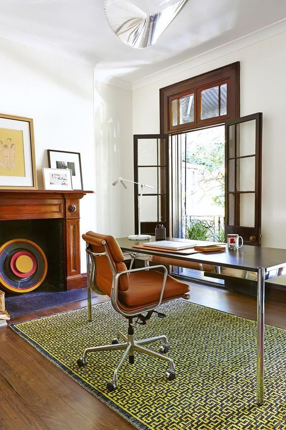 a mid century modern home office with an entrance to the blacony, a non working fireplace, a desk, an orange leather chair, a printed rug and chic artworks
