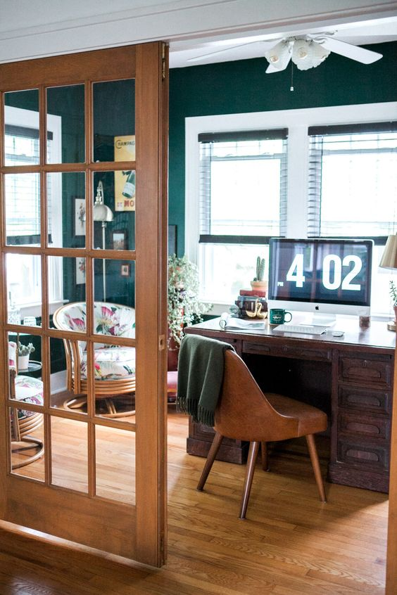 a mid-century modern home office with dark green walls, a dark stained desk, a leather chair, a gallery wall, floral chairs and potted plants