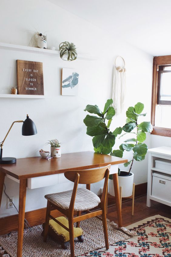a mid-century modern home office with rich-stained furniture, layered rugs, a potted plant, macrame, open shelves, artworks and a storage unit
