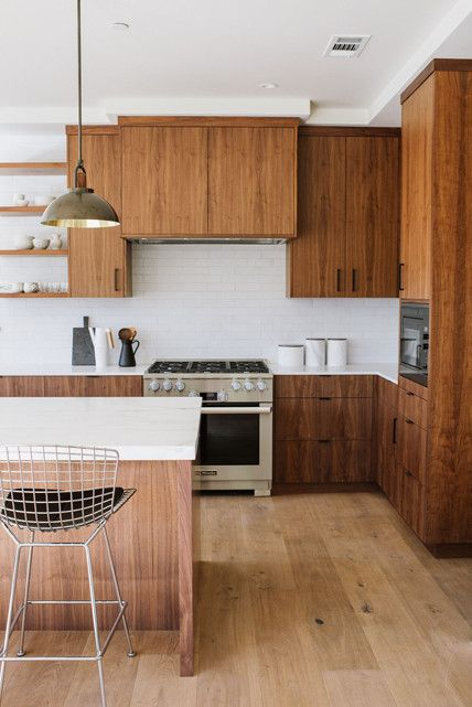 a mid-century modern kitchen with dark stained cabinets, a rich stained kitchen island, white stone countertops and a white skinny tile backsplash
