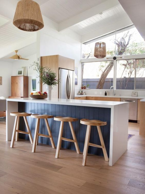 a mid-century modern kitchen with light stained cabinets, a white and navy kitchen island, white stone countertops, pendant lamps and a view