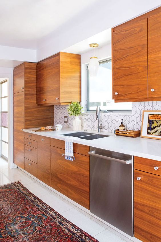 a mid-century modern kitchen with rich-stained cabinets, a geometric tile backsplash, white stone countertops and a printed rug