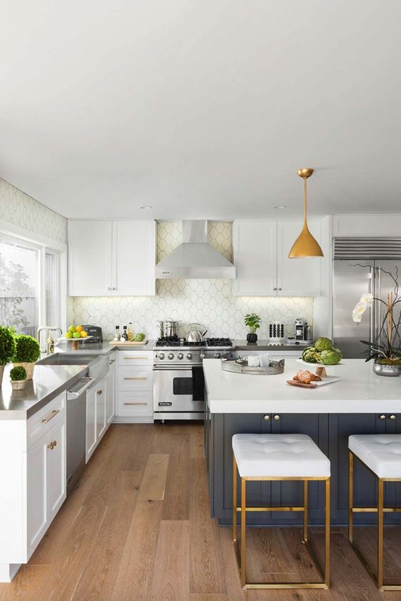 a mid-century modern kitchen with white cabinets, a white Moroccan tile backsplash, a navy kitchen island, white stools, pendant lamps and potted greenery