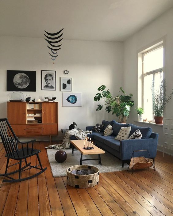 a mid-century modern living room with a blue sofa, a stained buffet, a black rocker, a low bench, a basket for storage and a cool gallery wall