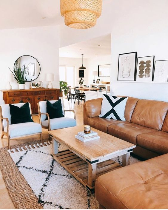 a mid-century modern living room with a boho feel, an amber leather sofa, neutral chairs, a wooden coffee table, printed textiles