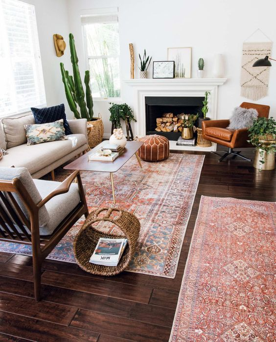 a mid-century modern living room with a non-working fireplace, a neutral sofa, an amber leather chair, baskets for storage and potted plants
