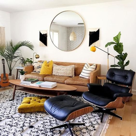 a mid-century modern living room with a tan leather sofa, a black leather chair, a printed rug and pillows, potted plants and a round mirror