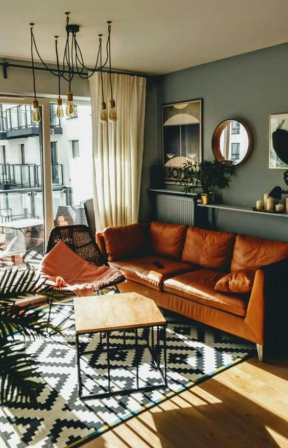 a mid-century modern living room with grey walls, an amber leather sofa, a black woven chair, an open shelf with decor and mirrors
