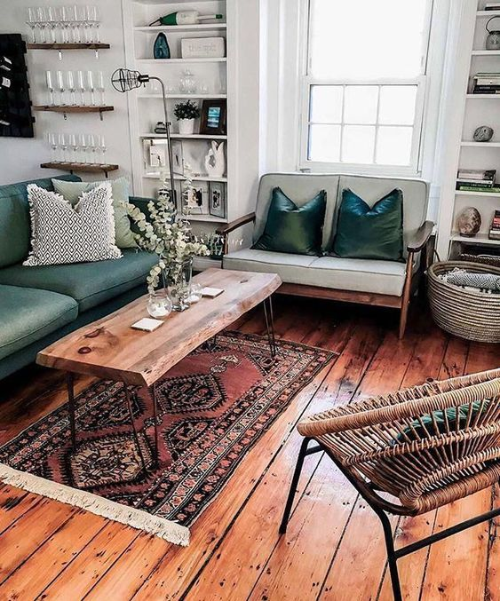 a mid-century modern sitting room with a light and dark green loveseat, a living edge table, a woven chair, a printed rug and built-in shelves