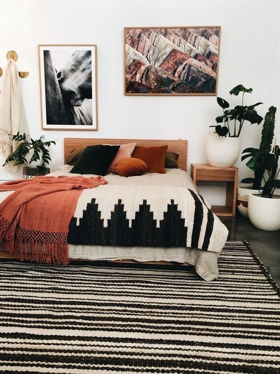 a mid-century modern to boho bedroom with a light stained bed and nightstands, printed bedding, bold artworks and potted plants