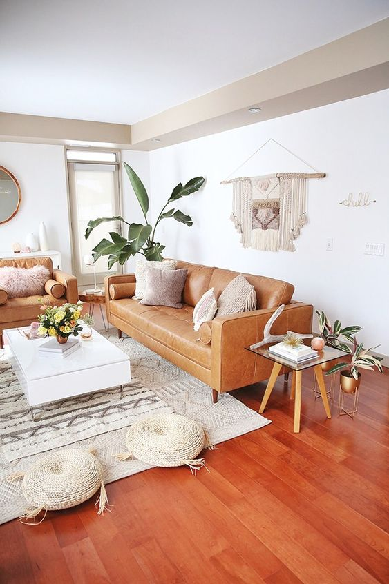a mid-century modern to boho living room with tan leather furniture, a low white coffee table, woven poufs, a macrame hanging and potted plants