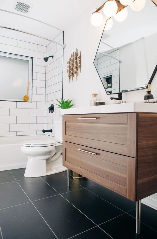 a mid-century modern with white and black tiles, a stained vanity, a hexagon mirror, a wall lamp and brass touches