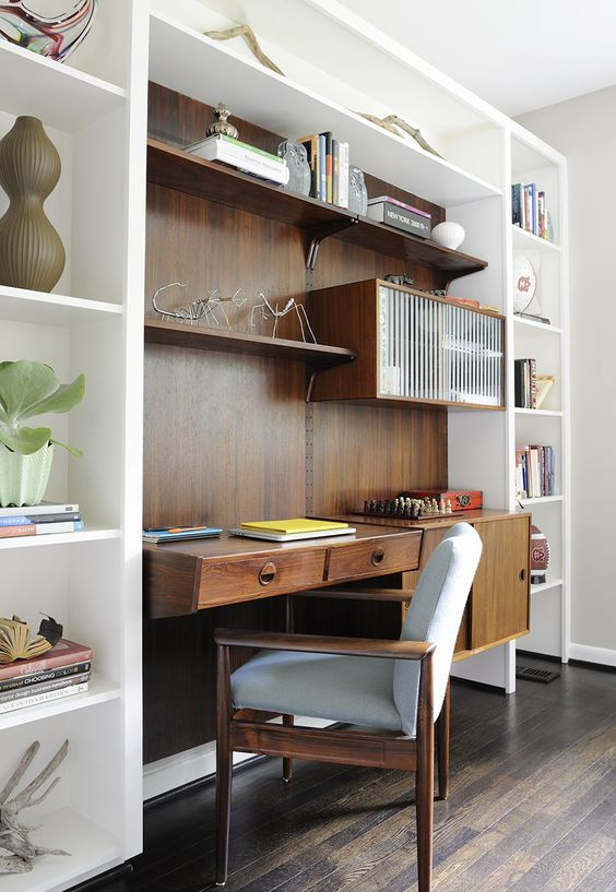a mid-century modern working nook with a stained desk and shelves, a cool chair and a large open storage unit around
